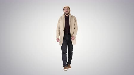 boyun : Handsome man in fashionable clothes walking and smiling on gradient background. Stok Video