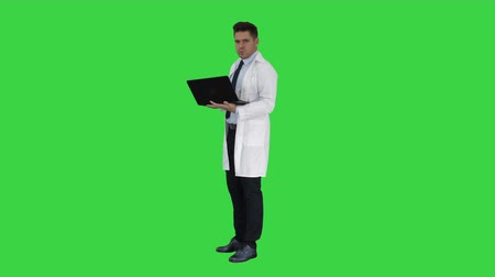 開業医 : Cheerfull doctor with laptop laughing after giving a serious look to camera on a Green Screen, Chroma Key.