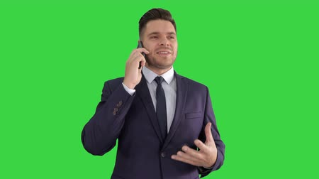 хмурый : Serious worried businessman talking on cellphone on a Green Screen, Chroma Key.