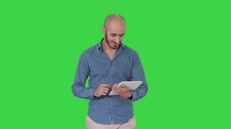 перегружены : Arabian man walking and using tablet surfing internet on a Green Screen, Chroma Key. Стоковые видеозаписи