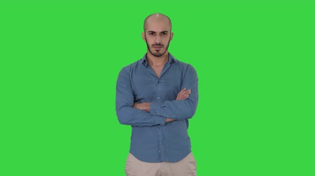 dobras : Serious confident arabian man in casual folds hands looking into camera on a Green Screen, Chroma Key.