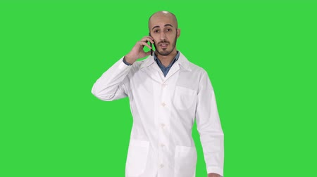 медик : Professional medical doctor talking on mobile phone while walking on a Green Screen, Chroma Key.
