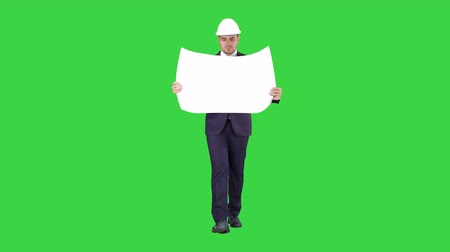 inspector : Professional architect is walking and holding blueprint The man is wearing helmet on a Green Screen, Chroma Key.