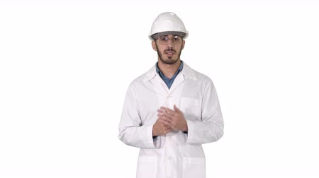 здесь : Scientist in white robe and helmet presenting pointing to side with hand and explaining to camera on white background.