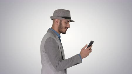 background young : Man walking with a phone and serfing internet on gradient background. Stock Footage