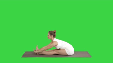 dorsal : Young sporty attractive woman practicing yoga, doing Seated forward bend exercise, paschimottanasana pose, working out, wearing sportswear on a Green Screen, Chroma Key. Stock Footage