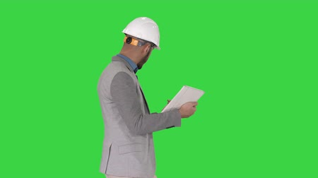 hardhat : The hipster engineer making video call with tablet showing result of his work on a Green Screen, Chroma Key.