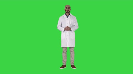 meia idade : Arab doctor man in medical coat talking and presenting with hand something on a Green Screen, Chroma Key. Vídeos