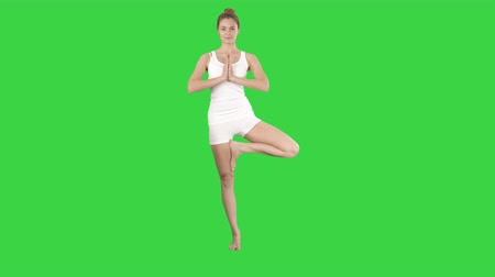 pilates : Tree pose, standing on one leg, hands in Namaste, prayer gesture on a Green Screen, Chroma Key. Stock Footage