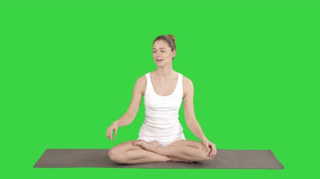 fulllength : Young attractive woman sitting in lotus pose and pointing at something or someone while talking on a Green Screen, Chroma Key.