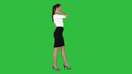 vysoká klíč : Beautiful young woman in elegant outfit walking, holding hands on hips on a Green Screen, Chroma Key.