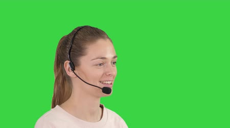 телемаркетинг : Beautiful call center operator with headset talking on a Green Screen, Chroma Key.