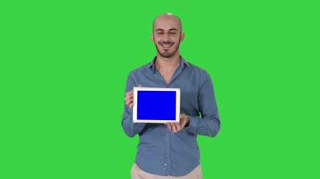 lezer : Arab man walking and showing tablet presenting something on a Green Screen, Chroma Key.