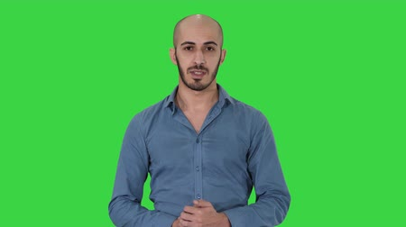 promover : Arabic young man in shirt talking presenting something and pointing to the side on a Green Screen, Chroma Key. Stock Footage
