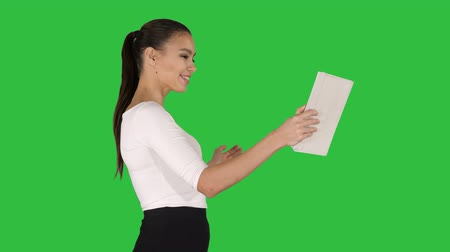 ebook : Happy woman making a video call with tablet on a Green Screen, Chroma Key.