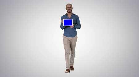 exibindo : Arab man walking and showing tablet presenting something on gradient background. Stock Footage