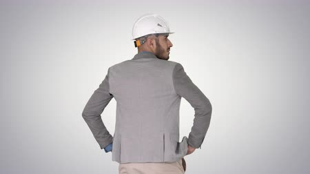 портретный : Engineer standing and looking around on gradient background. Стоковые видеозаписи