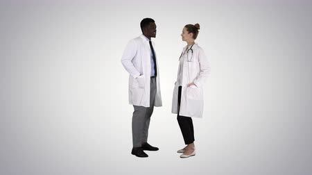 shaking hand : Two caucasian and afro american smiling doctors standing looking in to camera on gradient background. Stock Footage