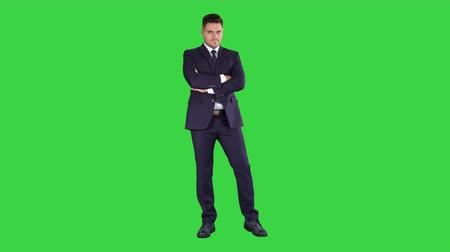 hajtogatott : Businessman with fo;ded hands looking to camera on a Green Screen, Chroma Key.