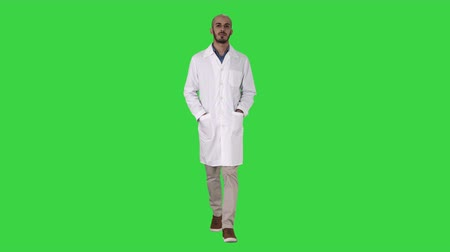 traje de passeio : Arab handsome doctor wearing his uniform walking with hands in pockets on a Green Screen, Chroma Key. Vídeos