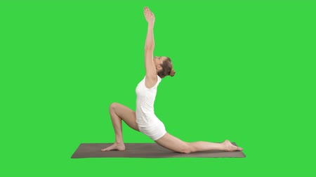 hilâl : Sporty attractive girl practicing yoga, standing in Horse rider exercise, anjaneyasana pose on a Green Screen, Chroma Key.
