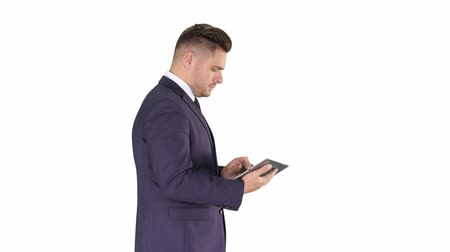 gravata : Elegant young businessman using his PC tablet while walking on white background. Stock Footage