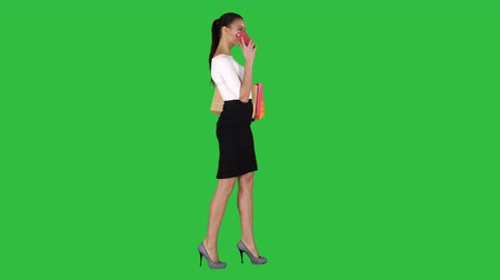 ключ : Young woman walking with shopping bags talking on mobile phone on a Green Screen, Chroma Key.