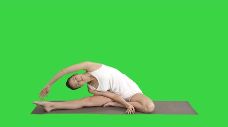 quadriceps : Beautiful young woman wearing white clothing doing yoga exercise Sitting in One-Legged King Pigeon (Single Pigeon) Pose on a Green Screen, Chroma Key.