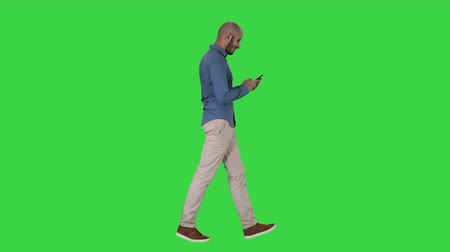 fulllength : Young man walking and using a phone on a Green Screen, Chroma Key.