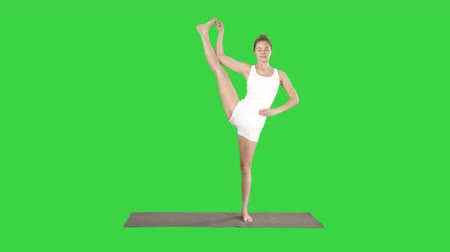 pilates : Beautiful smiling happy young woman doing yoga exercise on mat, standing in Vrksasana Posture, Tree Pose on a Green Screen, Chroma Key.