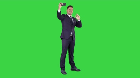 focus on foreground : Business man taking selfie on a Green Screen, Chroma Key.