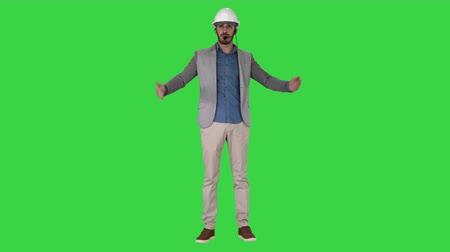 щит : Architect man in helmet and head set talking to camera and making gestures showing on some objects on a Green Screen, Chroma Key.