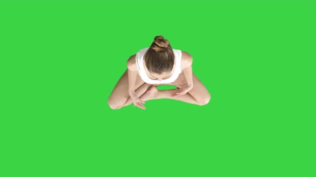 vysoká klíč : Beautiful woman sitting without yoga mat in lotus pose on a Green Screen, Chroma Key.