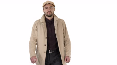 semana de moda : Fashionable man with dark beard in trench coat walking on white background.