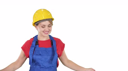 flexibilidade : Woman in construction helmet dancing on white background.