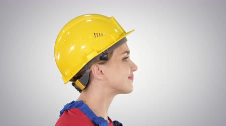 learning to walk : The young woman engineer with yellow safety helmet walking and smiling on gradient background. Stock Footage