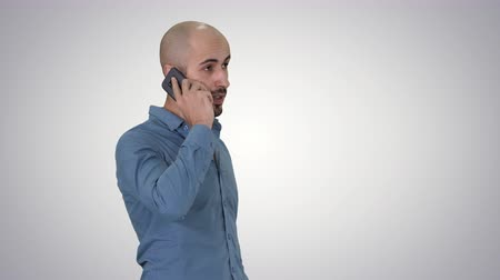 telefonda : Serious arab talking on the phone on gradient background.
