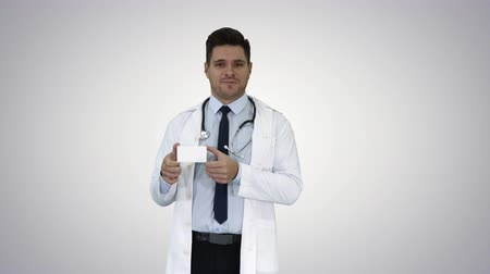 examining : Doctor talking to camera presenting new medicine on gradient background. Stock Footage