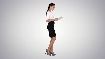 mirando pantalla : Attractive businesswoman using a digital tablet while walking on gradient background.