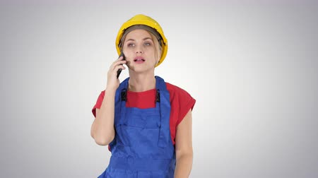 female measurements : Young female worker talking on phone while walking on gradient background.