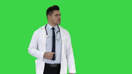 exibindo : Happy doctor showing something near him and smiling on a Green Screen, Chroma Key. Stock Footage
