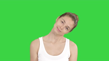 excesso : Smiling Woman Relaxing Her Neck Muscles Doing Stretching Exercise on a Green Screen, Chroma Key.
