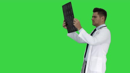 rezonans magnetyczny : Healthcare personnel in white labcoat, looking at x-ray radiographic image, ct scan, mri while walking on a Green Screen, Chroma Key.