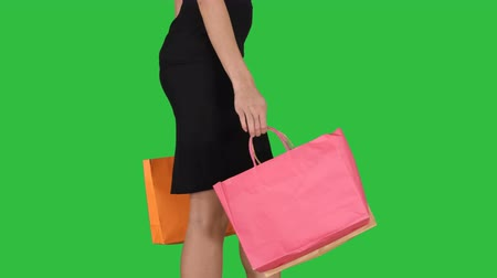 vysoká klíč : Young woman with shopping bags walking out from shop on a Green Screen, Chroma Key.