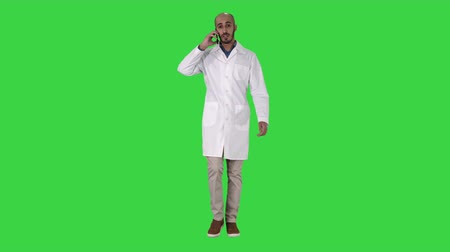 internar : Professional medical doctor talking on mobile phone while walking on a Green Screen, Chroma Key.