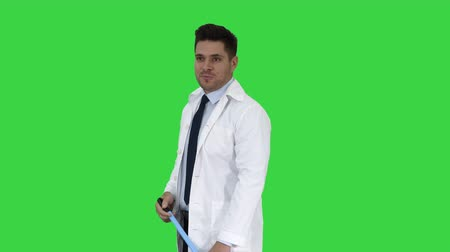 süpürge : Man in white robe sweeping the floor and talking on a Green Screen, Chroma Key. Stok Video