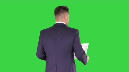 tela : Businessman walking and supervising the plan of the house on a Green Screen, Chroma Key.