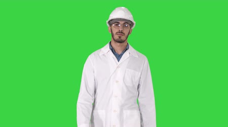 reflektör : Young engineer in robe and helmet putting glasses on while walking on a Green Screen, Chroma Key. Stok Video