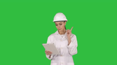 возобновляемый : Woman engineer checking information and objects on her tablet on a Green Screen, Chroma Key.