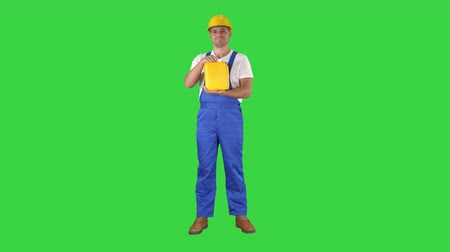 roadwork : Construction worker advertising construction material in canister on a Green Screen, Chroma Key.